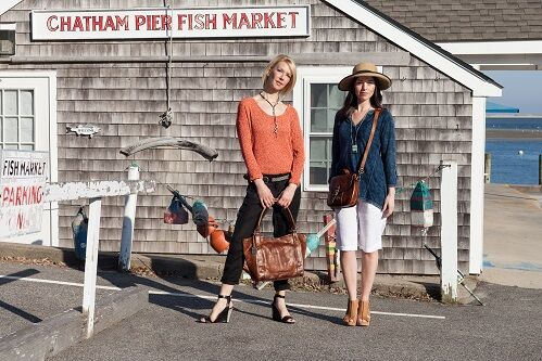 One blonde and one brunette women modeling clothes outside of 'CHATHAM PIER FISH MARKET'