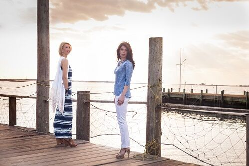 Two caucasian female models on a pier modeling East Coast fashion styles in front of a vast sky