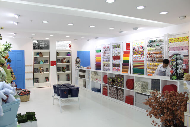 Full view of two adjacent walls inside the store, with shelves of goods of every color