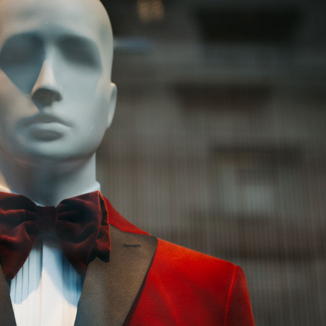 Mannequin with red suit and maroon bow tie