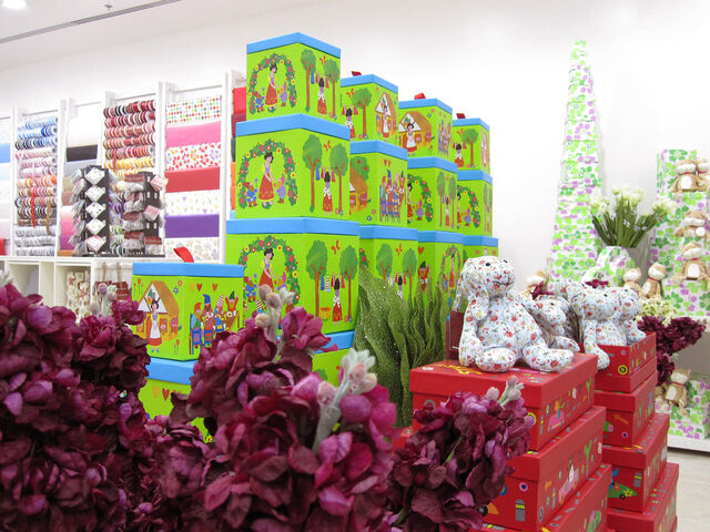 A large assortment of very colorful giftbags and giftwraps inside a white, well-lit store