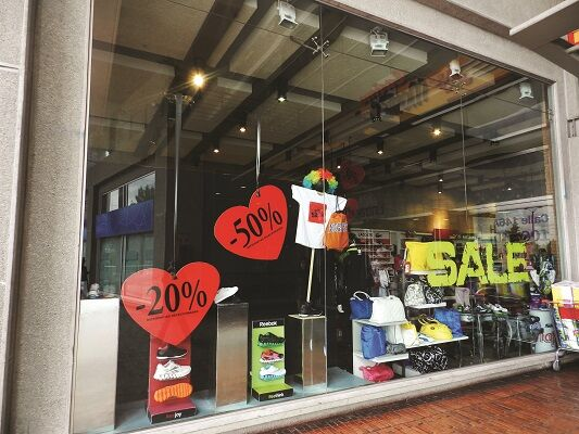 Exterior of a retail store with -20% and -50% 'SALE' signs placed on hearts in the window