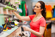 woman with ponytail shopping for athletic shoes